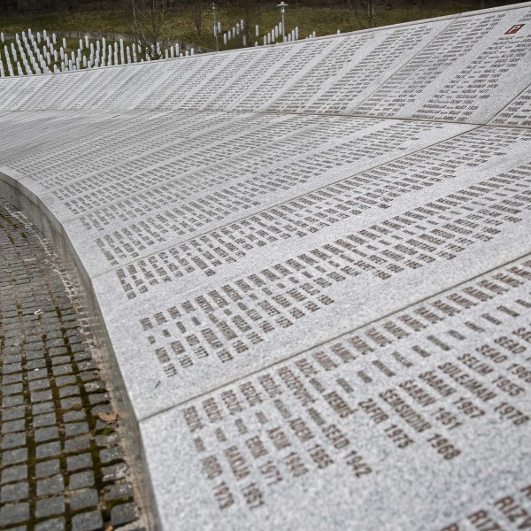 """<p>At three o'clock in the morning on July 6th, 1995, the VRS began its attack on Srebrenica. Advancing from the south, they set fire to the Bosniak homes and villages in their path, forcing thousands of civilians to flee to the UN base in Potocari where several hundred Dutch peacekeeping forces were stationed.</p> <p>Soldiers of the Army of the Republic of Bosnia and Herzegovina (ARBiH) were unable to prevent the Dutch troops from abandoning there posts, which fell one after another to the advancing Bosnian Serb Army (VRS). By July 9th, the VRS was poised just one kilometer outside the city center of Srebrenica. The next day the ARBiH launched a counterattack, briefly forcing the Serbs back to their starting positions. Their success, however, was short-lived.</p> <p>On July 11th, General Mladic entered Srebrenica with his troops, and declared before a throng of assembled journalists, """"We give this town to the Serb nation...the time has come to take revenge on the Turks in this region.""""</p> <p>That same night, around 15,000 Bosniak men set off from the areas of Sunsnjari and Jaglic through the forests in an attempt to reach free territory. Well over two-thirds of the men who embarked on this journey--which would come to be known as the Death March--were eventually captured and killed by the VRS.</p> <p>When VRS soldiers arrived to take control of the UN base in Potocari, they faced no resistance from the Dutch peacekeeping forces. Potocari had become completely overcrowded, with more than 6,000 civilians crammed inside the compound, and an additional 20,000 sheltering in surrounding building. Conditions inside the enclave were horrendous. In addition to the shortage of food and water, the Bosniak populations in Potocari faced unspeakable abuse at the hands of the VRS soldiers including torture, beatings, rape, and murder.</p> <p>VRS troops soon began to separate Bosniak men from their families. The women, children, and elderly--numbering over 25,000-- were loaded on"""